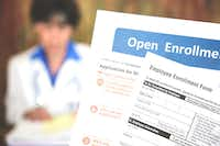 Patient holding open enrollment health care benefits forms with a medical doctor in the background. (iStockphoto/Getty Images)