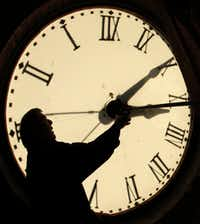 Custodian Ray Keen checks the time on a clock face after changing the time on the clock atop the Clay County Courthouse in Clay Center, Kan. in 2010.  (Charlie Riedel/Associated Press File Photo)