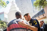 Dallas police Sgt. Dan Mosher comforts Odell Edwards, the father of Jordan Edwards, a 15-year-old who was killed by a Balch Springs police officer in April, during a day of remembrance for last year's police ambush organized by Faith Forward Dallas at Thanks-Giving Square on July 7, 2017, in Dallas.(Smiley N. Pool/Staff Photographer)