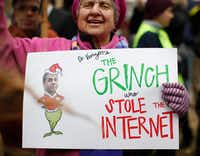 "Diane Tepfer holds a sign with an image of Federal Communications Commission Chairman Ajit Pai as the ""Grinch who Stole the Internet"" during protests in Washington, on Thursday. The FCC voted to eliminate net-neutrality protections for the internet(Carolyn Kaster/AP)"