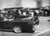 In this Nov. 22, 1963 file photo, the limousine carrying mortally wounded President John F. Kennedy races toward the hospital seconds after he was shot in Dallas.(Justin Newman/AP)