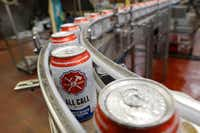 Cans of All Call, one of the core brands at Lakewood Brewing Co., make their way to a packaging technician on Dec. 6, 2017.(Ron Baselice/Staff Photographer)
