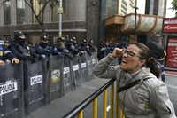 A demonstrator shouts slogans in front of the Senate building in Mexico City during a Dec. 14 protest against the potential approval of an Internal Security Law, which would allow the army to act as police. Mexican deputies approved a new security law that provides a legal framework for military deployment, and the controversial initiative is being discussed in the Senate. (Yuri Cortez/Agence France-Presse)