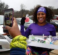 Scymentress Williams proudly displays a cookie recognizing her completion of running 2,017 miles during 2017, her New Year's resolution for this year. Next year? At least 2,018; more likely at least 2,100.(Steve Hamm/Special Contributor)
