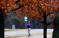 Scymentress Williams works to complete a yearlong New Years resolution to run 2,017 miles in 2017. The final half-mile of her long journey offered a plethora of fall color along her running path, almost as if nature was forming a welcoming finish line for her achievement. (Steve Hamm/Special Contributor)