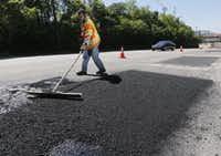 Dallas Street Services employees Gary Langley worked to fix part of deteriorated Harry Hines Boulevard on April 15, 2015.(File Photo/Staff)