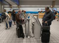 Travelers checked their luggage before boarding an American Airlines flight in Terminal C at DFW Airport on Monday.(Rex C. Curry/Special Contributor)