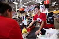Orlando Delgado, a cashier from the H-E-B in Laredo, checks out customers at the H-E-B grocery store in Rockport on Aug. 31.(Rose Baca/Staff Photographer)