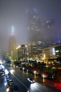 Fog settled over the historic Mercantile Building (left) and Comerica Bank Tower (center) and Main Street Garden Park in downtown Dallas on Monday evening.(Tom Fox/Staff Photographer)