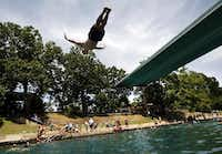 <p>Todd Mouser of Los Angeles dives at Barton Springs Pool during a free swim day.</p>(Ricardo B. Brazziell/Austin American-Statesman)