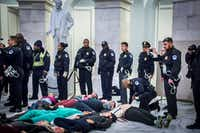 "About 70 protesters against the GOP tax bill were arrested Monday while staging a ""die-in"" in the rotunda of the Rayburn House office building.(Michael Nigro/TNS)"
