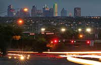 Traffic zips by a view of the Dallas skyline from north of Royal Lane and Abrams Road in Lake Highlands. (Louis DeLuca/Staff Photographer)