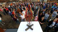 "People look at a design for the 30-foot memorial sculpture ""Phoenix"" designed by Troy Connatser during a first anniversary remembrance event at Schrade Bluebonnet Park last Dec. 26 in Rowlett.(Jae S. Lee/Staff Photographer)"