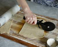 Using a pizza cutter, cut the dough into small squares.(Ron Baselice/Staff Photographer)
