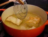 The dough is cooked in oil until golden brown.(Ron Baselice/Staff Photographer)
