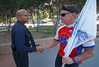 John Lawton (left), an assistant chief who's now a major, shook hands with a retired police officer riding in a memorial bike ride in April.(Jae S. Lee/Staff Photographer)