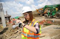 Amanda Calvert, an intern with Skanska construction, takes a photo of the construction progress while walking the perimeter of the job site she is working on, The Music Factory in Irving.(Rose Baca/Staff Photographer)