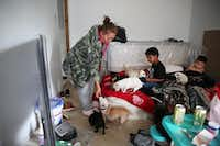 Petra Cervantes feeds marshmallows to her dogs while her grandsons Josiah Jackson, 4, (left) and Aaron Cervantes, 3, watch TV in their home in East Houston. The family recently moved back into the house after it was flooded during Hurricane Harvey. Before that, they were living in a tent on their property while waiting to have basic repairs done. (Rose Baca/Staff Photographer)