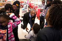 """Williams Chicken CEO and founder Hiawatha Williams (center) and his wife, Doris, (top left) hugged the children of slain Dollar General clerk Gabrielle Monique Simmons during a shopping spree the couple organized at a Target store on Friday. The children and Simmons' fiance were treated to lunch and the surprise spree with money raised by the Williams Chicken """"Change for Change"""" campaign.(Smiley N. Pool/Staff Photographer)"""