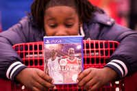 Martavionne Parker, 11, checked out a PlayStation game during the Target shopping spree.(Smiley N. Pool/Staff Photographer)