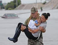 Houston SWAT officer Daryl Hudeck carries Catherine Pham and her son 13-month-old son Aidan to safety after they were rescued via boat from the flooding on Interstate 610 south in Houston on Sunday, August 27, 2017. (Louis DeLuca/Staff Photographer)