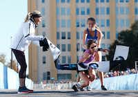 Shalane Flanagan, four-time Olympian, left, watches as Chandler Self, winner of the full marathon, is helped by relay runner Ariana Luterman, 17, from Greenhill School, at the finish line during the BMW Dallas Marathon in downtown Dallas, Sunday, Dec. 10, 2017. (Nathan Hunsinger/Staff Photographer)