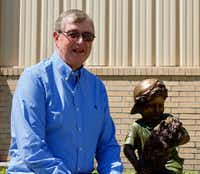 "Jim with a sculpture that represents his grandfather, LeRoy ""Hallie"" Garwood, who was an orphan train rider in 1911.(Bruce N. Meyer/Special Contributor)"