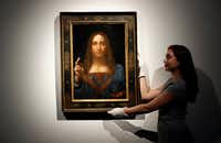 "An employee poses Oct. 24 with Leonardo da Vinci's <i>Salvator Mundi</i> on display at Christie's auction rooms in London. An official in the United Arab Emirates said the new Louvre museum in Abu Dhabi is ""very proud"" to have acquired a painting by Leonardo da Vinci that sold for a staggering $450 million last month.(Kirsty Wigglesworth/The Associated Press)"