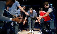 Dallas Mavericks forward Dirk Nowitzki slaps hands with fans and teammates as he is introduced before the Los Angeles Lakers game at American Airlines Center.(Tom Fox/Staff Photographer)