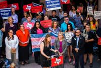 Ashley Smith (bottom center, at the mike), who is transgender, speaks to protesters rallying against the bathroom bill on the fourth day of a special legislative session July 21 at the Texas state capitol in Austin. Smith's photo with Gov. Greg Abbott went viral; she noted that he didn't know she was transgender. To the right of Smith is Sen. Sylvia Garcia.(Ashley Landis/Staff Photographer)