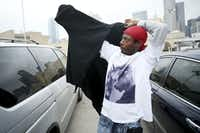 Elton Pearson tries on a donated jacket in a parking lot along Cadiz Street.(Andy Jacobsohn/Staff Photographer)