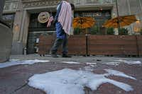 A homeless man carrying a blanket walks by ice on sidewalk in downtown Dallas on Monday.(Jae S. Lee/Staff Photographer)