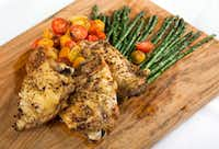 Oven baked chicken thighs with roasted asparagus and cherry tomatoes(Ashley Landis/Staff Photographer)