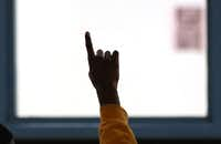 A juvenile offender raises his hand to ask a question during a group session, as seen during a tour of  the Dr. Jerome McNeil Jr. Detention Center inside the Henry Wade  Juvenile Justice Center, Dallas County's largest juvenile detention center, photographed on Aug. 17, 2017.(Louis DeLuca/Staff Photographer)