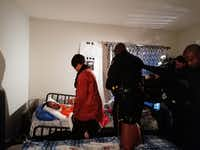 Police Chief U. Renee Hall, in red coat, visits Ayodeji Adekilekun, as he was named Dallas Police Chief of the Day on Jan. 5, 2018. He was once counted among the star students at his middle school, but a terminal brain cancer diagnosis has kept him confined to his bed, in hospice care, since November.(Gloria Adekilekun/Courtesy)