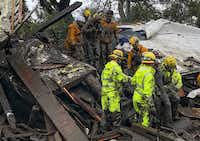 Emergency workers rescue a 14-year-old girl, right, after she was trapped inside a home destroyed by a mudslide in Montecito, Calif., Jan. 9, 2018. Drenching rain sent mud roaring down the hillsides of Santa Barbara County on Tuesday, killing at least five people, carrying houses off their foundations, snapping telephone poles and wrapping vehicles around trees, the authorities said.(Mike Eliason/Santa Barbara County Fire Department)