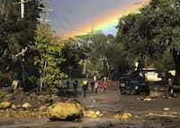 In this photo provided by Santa Barbara County Fire Department, shows a rainbow forming above Montecito, Calif. while law enforcement and the curious survey the destruction on Hot Springs Road on Tuesday, Jan. 9, 2018.(Mike Eliason/Santa Barbara County Fire Department)