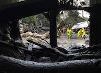 In a Santa Barbara County Fire Department photo, emergency workers look through debris of structures destroyed by a mudslide in Montecito, Calif., Jan. 9, 2018.(Mike Eliason/Santa Barbara County Fire Department)