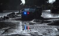 A police vehicle drives across a flooded side road off the US 101 freeway near the San Ysidro exit in Montecito, California on January 9, 2018.(Frederic J. Brown/Agence France-Presse)