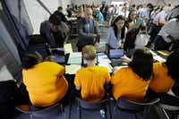 In this Wednesday, Aug. 2, 2017, file photo, job candidatessign in for a job fair at the Amazon fulfillment center in Robbinsville Township, N.J. (Julio Cortez/AP)