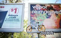 A VBike rental bike is left up on an elevated billboard along West Lawther Drive in Dallas on Oct. 23, 2017. (Rose Baca/Staff Photographer)