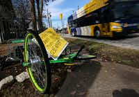 A sign advertising shelled pecans is stuck through an overturned LimeBike on the sidewalk along Henderson Avenue in Dallas on Dec. 21, 2017. (Rose Baca/Staff Photographer)
