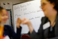 <p>TheRev. Holly Bandel, First United Methodist Church of Dallas' associate minister for mission and advocacy, fist bumps a student as she helps her learn to read at J.J. Rhoads Learning Center.</p>(Nathan Hunsinger/The Dallas Morning News)