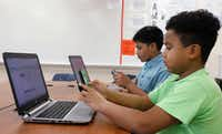 Sixth-graders Hemant Pacha (left), 11, and Mikey Shands, 11, work on their phones and computers in a computer coding club at Barbara Bush Middle School in Irving. They both create an app for games and Mikey has his own YouTube channel. Hemant wants to be a doctor and a part-time video game designer and Mikey wants to be a cartoon animator. (David Woo/Staff Photographer)