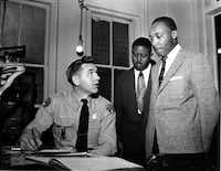 The Rev. Martin Luther King Jr. (right), accompanied by the Rev. Ralph D. Abernathy, is booked by city police Lt. D.H. Lackey in Montgomery, Ala., on Feb. 23, 1956.  The civil rights leaders were arrested on indictments by a grand jury in the bus boycott. (File Photo/The Associated Press)