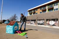 Dallas artist Giovanni Valderas places one of the pieces of his project called 'Casitas Tristas' on Fort Worth Drive in Dallas on Jan. 14(Nathan Hunsinger/Staff Photographer)