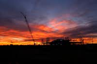 The sun sets behind AT&T Stadium and the Texas Live! construction site in Arlington.(Jae S. Lee/Staff Photographer)