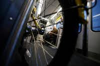 Melody Townsel, who teaches AP English at Booker T. Washington High School for the Performing and Visual Arts, is seen through the wheel of a rental bike while she rides the DART train home after maneuvering her wheelchair past rental bikes in downtown Dallas.(David Woo/Staff Photographer)