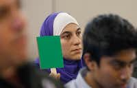 Alia Shakir holds up a green sign in solidarity with one of the speakers at the McKinney ISD board meeting Tuesday. The other side of the sign is red if a member of the crowd doesn't agree with a speaker.(Ron Baselice/Staff Photographer)