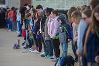 Students and community members hold hands in prayer before classes at Paducah Tilghman High School in Paducah, Ky., on Wednesday. The gathering was held for the victims of the Marshall County High School shooting on Tuesday.(Ryan Hermens/The Paducah Sun)